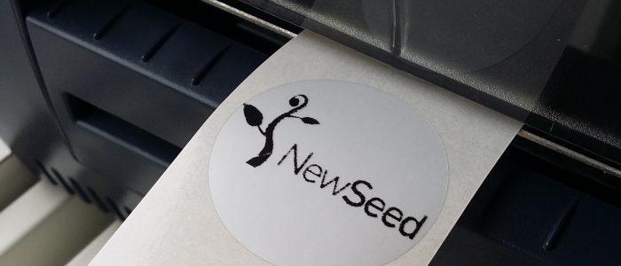 ZEBRA-utskrift av New Seeds logotyp på runt märke.